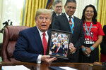 President Donald Trump shows off a gift during and event to sign an executive order establishing the Task Force on Missing and Murdered American Indians and Alaska Natives, in the Oval Office of the White House, Tuesday, Nov. 26, 2019, in Washington. (AP Photo/ Evan Vucci)