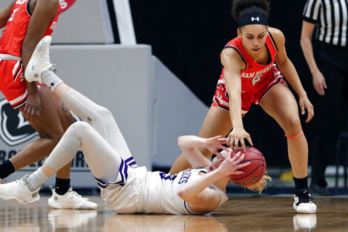 Stephen F. Austin guard Stephanie Visscher (13) has the loose ball knocked away by Sam Houston State forward Amber Leggett, right, during the second half of an NCAA college basketball game for the Southland Conference women's tournament championship Sunday, March 14, 2021, in Katy, Texas. (AP Photo/Michael Wyke)