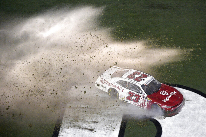 John Hunter Nemechek (23) sprays turf while sliding through the grass in front of the grandstands after losing control of his car during a NASCAR Xfinity Series auto race at Daytona International Speedway, Friday, July 5, 2019, in Daytona Beach, Fla. (AP Photo/Phelan M. Ebenhack)