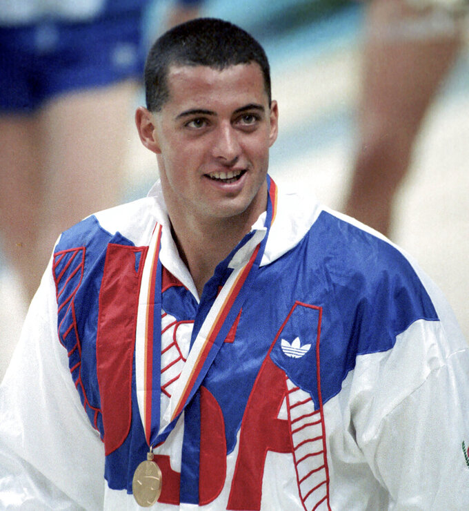 FILE - In this Sept. 21, 1988, file photo, Matt Biondi, of the United States, wears his Olympic gold medal during awarding ceremonies after the men's 800-meter freestyle relay at the Summer Olympic Games in Seoul, Korea. Bitter at the resistance he faced for trying to transform the sport of swimming, Biondi turned his back on the sport in the early 1990s. Now, he is back at the pool, leading a new organization that hopes to improve the state of swimmers who have long been mere afterthoughts to those who make all the important decisions and cash in on their efforts. (AP Photo/Eric Risberg, File)