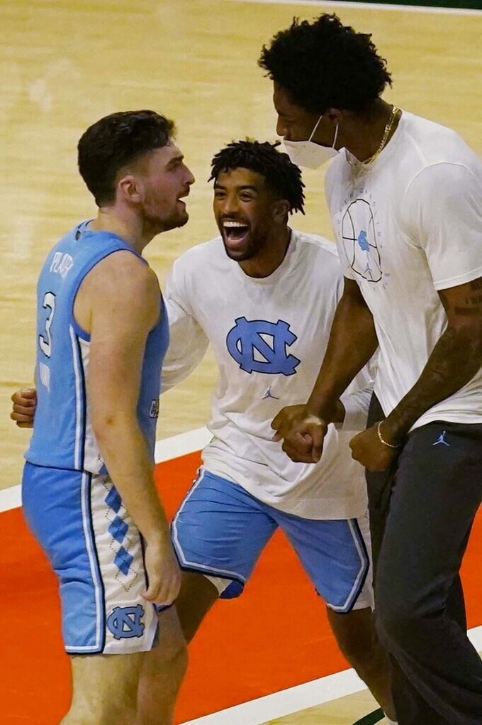 Teammates congratulate guard Andrew Platek (3) after he scored the winning basket during the second half of an NCAA college basketball game against Miami, Tuesday, Jan. 5, 2021, in Coral Gables, Fla. North Carolina defeated Miami 67-65. (AP Photo/Marta Lavandier)