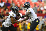 Baltimore Ravens quarterback Lamar Jackson, right, hands the ball to teammate running back J.K. Dobbins (27), left, during the first half of a preseason NFL football game against the Washington Football Team, Saturday, Aug. 28, 2021, in Landover, Md. (AP Photo/Nick Wass)