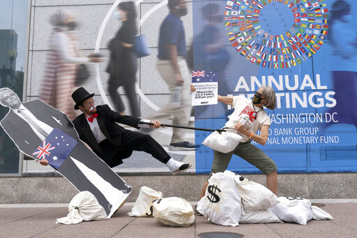 Activists holding a cardboard cutouts of Australian Prime Minister Scott Morrison protest outside of the International Monetary Fund headquarters during the World Bank/IMF Annual Meetings in Washington, Wednesday, Oct. 13, 2021. (AP Photo/Jose Luis Magana)