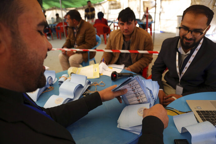 Afghan election workers check ballot papers of September's presidential election during the recounting process of ballot papers at Independent Election Commission counting center, in Kabul, Afghanistan, Tuesday, Nov. 12, 2019. Polling was held on Sept. 28, but the announcement of results repeatedly postponed after accusations of misconduct and technical issues with counting ballots. (AP Photo/Rahmat Gul)