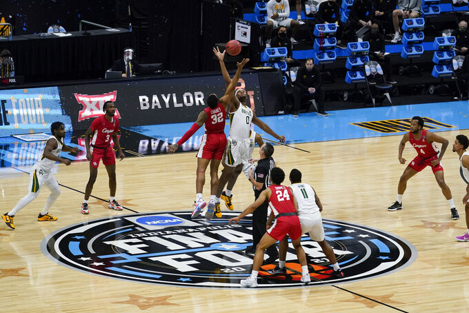 Houston forward Reggie Chaney (32) fights for the opening tipoff with Baylor forward Flo Thamba (0) during the first half of a men's Final Four NCAA college basketball tournament semifinal game, Saturday, April 3, 2021, at Lucas Oil Stadium in Indianapolis. (AP Photo/Michael Conroy)
