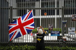 A protester hangs posters near a British flag tied to the fence at the Central Government Office building in Hong Kong on Thursday, July 4, 2019. Hong Kong police have announced the arrest of 12 people who tried to disrupt a ceremony Monday marking the anniversary of Hong Kong's return from Britain to China in 1997, and a person was arrested for his alleged involvement in the storming of the legislature building that night.(AP Photo/Andy Wong)