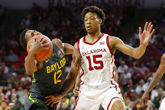 Baylor guard Jared Butler (12) drives around Oklahoma guard Alondes Williams (15) during the first half of an NCAA college basketball game in Norman, Okla., Tuesday, Feb. 18, 2020. (AP Photo/Sue Ogrocki)