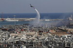 An army helicopter drops water at the scene of Tuesday's massive explosion that hit the seaport of Beirut, Lebanon, Wednesday, Aug. 5, 2020. (AP Photo/Hussein Malla)