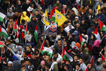 Palestinians wave national flags as they take part in a protest against President Donald Trump's Mideast initiative in the West Bank city of Ramallah. Tuesday, Feb. 11, 2020. Palestinian President Mahmoud Abbas plans to deliver a speech at the U.N. later in the day, but members will not be voting on a draft resolution. Palestinian officials denied the resolution had been pulled, but diplomats said many members, including European countries, rejected the language in a draft that had circulated. (AP Photo/Majdi Mohammed).
