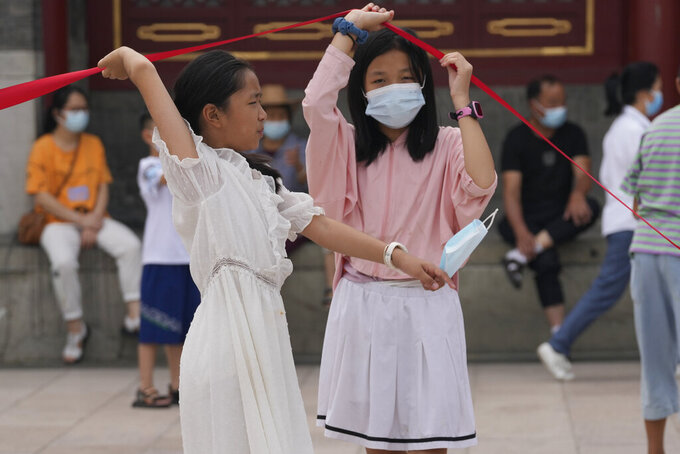 Children with masks lift up a barrier in Beijing Tuesday, Aug. 3, 2021. The coronavirus's delta variant is challenging China's costly strategy of isolating cities, prompting warnings that Chinese leaders who were confident they could keep the virus out of the country need a less disruptive approach. (AP Photo/Ng Han Guan)