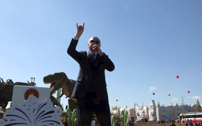 Turkey's President Recep Tayyip Erdogan speaks in front of a model dinosaur during the inauguration of a theme park in Ankara, Turkey, Wednesday, March 20, 2019. Erdogan has sparked a diplomatic spat with New Zealand and Australia as he campaigns for votes in local elections this month and portrays the mosque shooting in New Zealand and a World War I battle as targeting Islam.(AP Photo/Burhan Ozbilici)