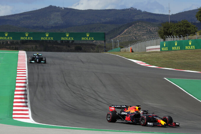 Red Bull driver Max Verstappen of the Netherlands takes a curve followed by Mercedes driver Valtteri Bottas of Finland, left, during the qualifying session ahead of the Portugal Formula One Grand Prix at the Algarve International Circuit near Portimao, Portugal, Saturday, May 1, 2021. The Portugal Grand Prix will be held on Sunday. (AP Photo/Manu Fernandez)