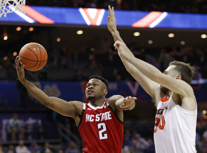 North Carolina State's Torin Dorn (2) drives against Virginia's Jay Huff (30) during the first half of an NCAA college basketball game in the Atlantic Coast Conference tournament in Charlotte, N.C., Thursday, March 14, 2019. (AP Photo/Nell Redmond)