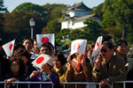 Japanese well-wishers hold Japanese national flag at the Imperial Palace before the royal parade of Japanese Emperor Naruhito and Empress Masako in Tokyo, Sunday, Nov. 10, 2019. (AP Photo/Eugene Hoshiko)