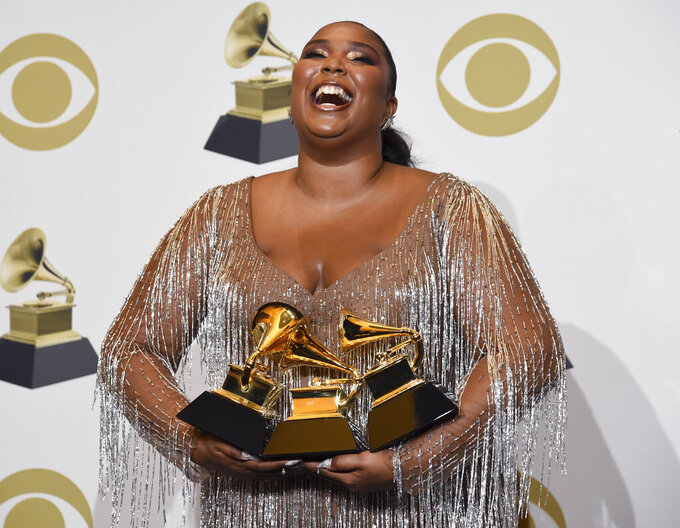 """Lizzo poses in the press room with the awards for best pop solo performance for """"Truth Hurts"""", best urban contemporary album for """"Cuz I Love You"""" and best traditional R&B performance for """"Jerome"""" at the 62nd annual Grammy Awards at the Staples Center on Sunday, Jan. 26, 2020, in Los Angeles. (AP Photo/Chris Pizzello)"""