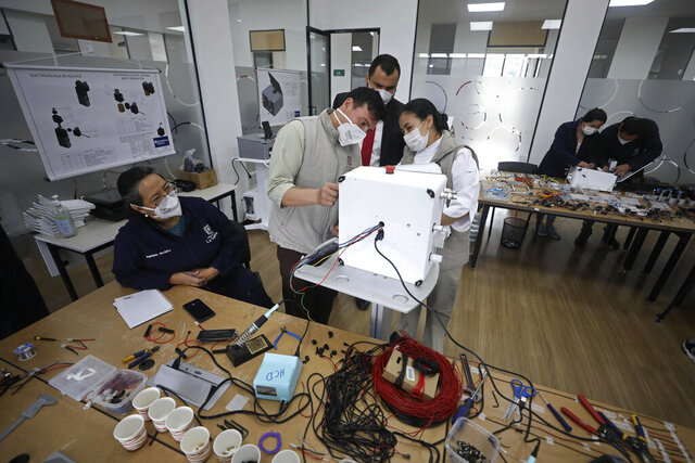 Engineering faculty and workers at La Sabana University work on a low-cost ventilator for patients with COVID-19 in Bogota, Colombia, Monday, July 6, 2020. The machine called the Heron looks like many other ventilators used to treat COVID-19 patients, but this device costs about $4,000, a fifth of the price of ventilators imported from China, and it's made in Colombia, where some hospitals have been overwhelmed by coronavirus patients. (AP Photo/Fernando Vergara)