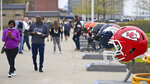 People walk past 32 NFL teams' helmets displayed for the NFL Draft, Saturday, April 24, 2021, in Cleveland. There will be a limit of 50,000 fans per day —- the league estimates it would have drawn up to 400,000 over three days in a non-pandemic year _ allowed on site to watch and enjoy the interactive NFL Draft Experience, which gives fans a chance to go inside the Browns' stadium and attempt a field goal or take a photo with the Lombardi Trophy. (AP Photo/Tony Dejak)