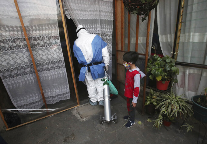 City worker Carlos Ruiz delivers a tank of oxygen to a COVID-19 patient, in the Iztapalapa borough of Mexico City, Friday, Jan. 15, 2021. The city offers free oxygen refills for COVID-19 patients. (AP Photo/Marco Ugarte)