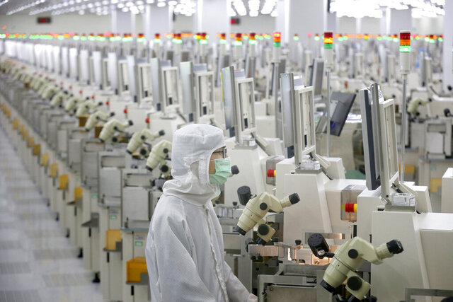In this Feb. 20, 2020, photo, a worker sits at a production line at a microelectronics factory in Nantong in eastern China's Jiangsu Province. China on Friday suspended more punitive tariffs on imports of U.S. industrial goods in response to a truce in its trade war with Washington that threatened global economic growth. (Chinatopix via AP)