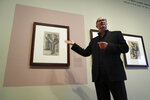 """Senior researcher Teio Meedendorp gestures during the presentation of Study for """"Worn Out"""", left, a drawing by Dutch master Vincent van Gogh, dated Nov. 1882, going on public display for the first time at the Van Gogh Museum in Amsterdam, Netherlands, Thursday, Sept. 16, 2021. (AP Photo/Peter Dejong)"""