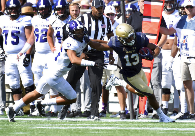 Navy's Chance Warren (13) stiff arms Holy Cross' Walter Reynolds in the first quarter of an NCAA college football game, Saturday, Aug. 31, 2019, in Annapolis, Md. (Paul W. Gillespie/Capital Gazette via AP)