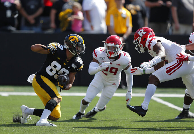 Iowa wide receiver Nico Ragaini, left, runs the ball on a kickoff return as Rutgers defensive backs Lawrence Stevens, center, and Tre Avery, right, defend during the first half of an NCAA college football game, Saturday, Sept. 7, 2019, in Iowa City. (AP Photo/Matthew Putney)