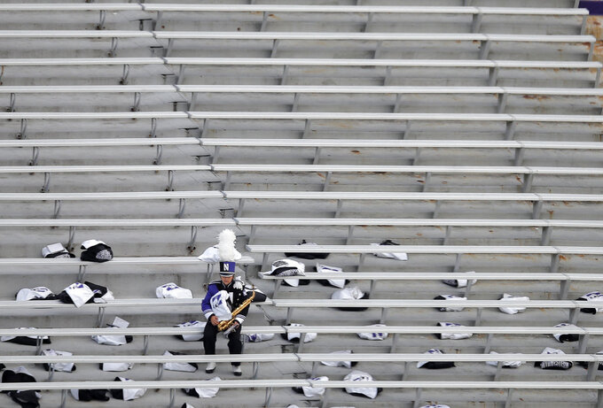 A member of the Northwestern University band waits in stands for the start of an NCAA college football game between Northwestern and Notre Dame Saturday, Nov. 3, 2018, in Evanston, Ill. (AP Photo/Jim Young)