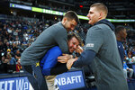 Denver Nuggets forward Juan Hernangomez, left, jumps onto the back of Dallas Mavericks forward Luka Doncic, center, as Nuggets center Nikola Jokic stands next to them before an NBA basketball game Thursday, March 14, 2019, in Denver. (AP Photo/David Zalubowski)