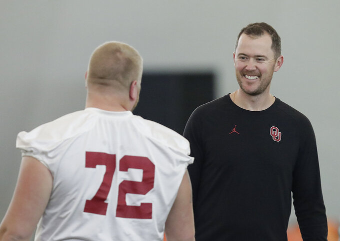 Oklahoma head coach Lincoln Riley, right, talks with Oklahoma offensive lineman Ben Powers during an NCAA college football practice Thursday, Dec. 27, 2018, in Davie, Fla. Oklahoma plays Alabama in the Orange Bowl on Dec. 29. (AP Photo/Brynn Anderson)