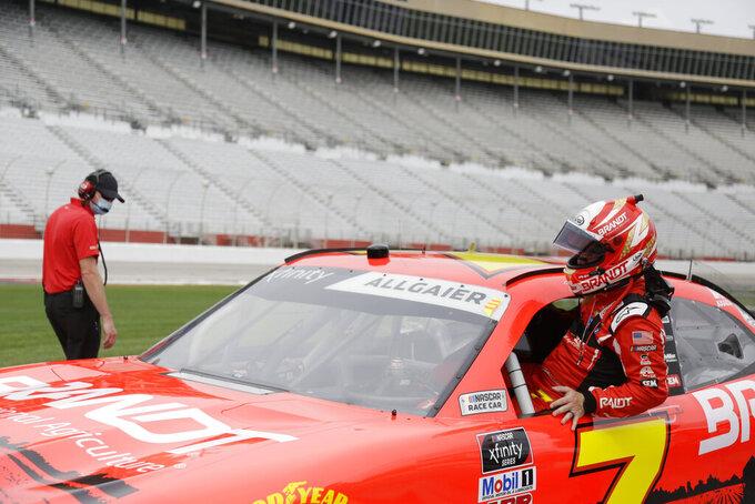 Justin Allgaier, right, gets into his car before a NASCAR Xfinity Series auto race at Atlanta Motor Speedway, Saturday, June 6, 2020, in Hampton, Ga. (AP Photo/Brynn Anderson)