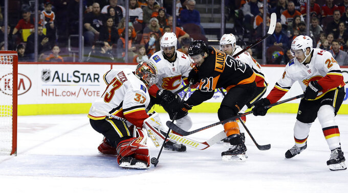 Philadelphia Flyers' Scott Laughton (21) cannot get the puck past Calgary Flames' David Rittich (33) as Oliver Kylington (58), Sam Bennett (93) and Travis Hamonic (24) defend during the second period of an NHL hockey game, Saturday, Jan. 5, 2019, in Philadelphia. (AP Photo/Matt Slocum)