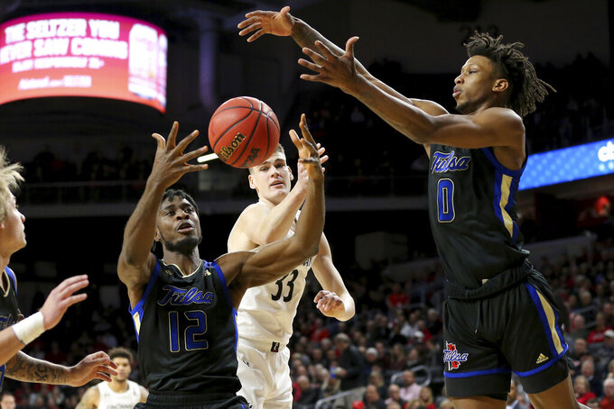 Tulsa center Emmanuel Ugboh (12) and guard Brandon Rachal (0) collect a rebound away from Cincinnati center Chris Vogt (33) during the first half of an NCAA college basketball game Wednesday, Jan. 8, 2020, in Cincinnati. (Kareem Elagazzar/The Cincinnati Enquirer via AP)