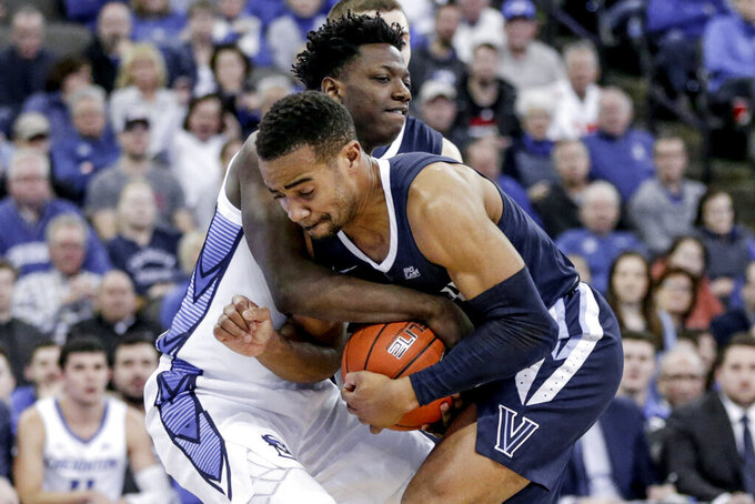 Villanova's Phil Booth, front, and Creighton's Kaleb Joseph, rear, struggle for the ball during the second half of an NCAA college basketball game in Omaha, Neb., Sunday, Jan. 13, 2019. (AP Photo/Nati Harnik)