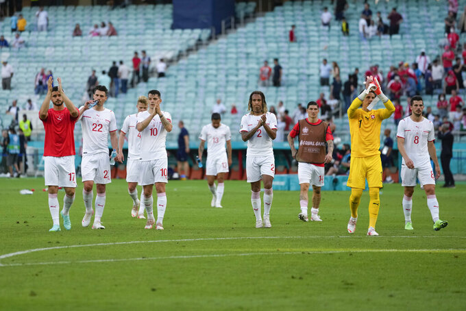 Switzerland players applaud fans at the end of the Euro 2020 soccer championship group A match between Wales and Switzerland, at the Baku Olympic stadium, in Baku, Azerbaijan, Saturday, June 12, 2021. The match ended in a 1-1 draw. (AP Photo/Darko Vojinovic, Pool)