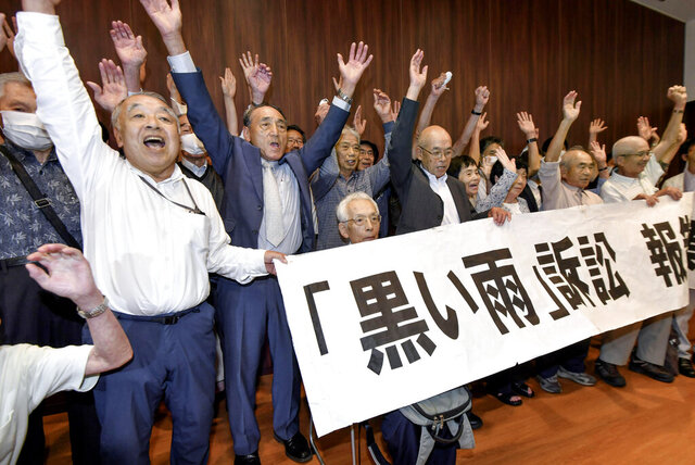"""A group of plaintiffs and supporters celebrate during a meeting following the court ruling in Hiroshima, western Japan, Wednesday, July 29, 2020. A court has recognized people exposed to radioactive """"black rain"""" that fell after the U.S. atomic attack on Hiroshima as atomic bomb survivors, ordering the government to provide the same medical benefits it gives other survivors. (Kyodo News via AP)"""