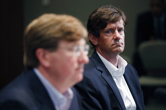 State Health Officer Dr. Thomas Dobbs, right, listens as Republican Gov. Tate Reeves lessens a number of social and business restrictions from previous executive orders dealing with the early days of COVID-19, during his daily update Monday, May 4, 2020, in Jackson, Miss. (AP Photo/Rogelio V. Solis)