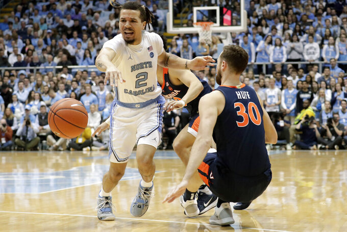 North Carolina's Cole Anthony (2) goes for the ball against Virginia's Jay Huff (30) during the first half of an NCAA college basketball game in Chapel Hill, N.C., Saturday, Feb. 15, 2020. (AP Photo/Chris Seward)