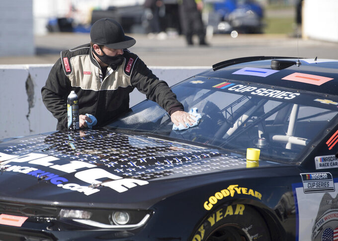 A pit member for Josh Bilicki (7) cleans his windshield before a NASCAR Cup Series auto race at Martinsville Speedway in Martinsville, Va., Sunday, Nov. 1, 2020. (AP Photo/Lee Luther Jr.)
