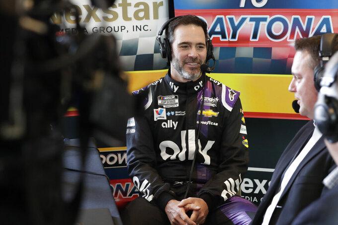 Jimmie Johnson, center, takes part in a radio interview during NASCAR Daytona 500 auto racing media day at Daytona International Speedway, Wednesday, Feb. 12, 2020, in Daytona Beach, Fla. (AP Photo/John Raoux)