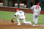 Texas Rangers first baseman Todd Frazier (21) reaches out for the throw to the bag as Los Angeles Angels' Mike Trout (27) reaches for a single in the sixth inning of a baseball game in Arlington, Texas, Saturday, Aug. 8, 2020. (AP Photo/Tony Gutierrez)