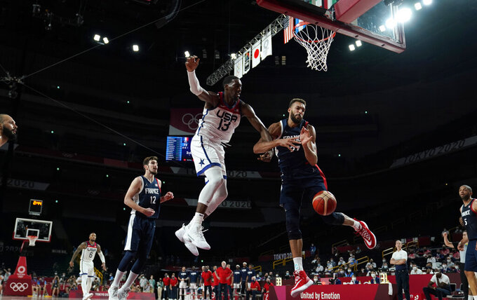 United States' Bam Adebayo (13) and France's Rudy Gobert (27) fight for a rebound during men's basketball gold medal game at the 2020 Summer Olympics, Saturday, Aug. 7, 2021, in Saitama, Japan. (AP Photo/Charlie Neibergall)