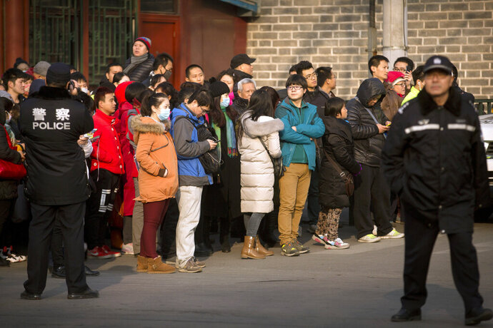 FILE - In this Jan. 1, 2016, file photo, Chinese policemen watch as depositors from Ezubao gather outside the State Bureau for Letters and Calls Reception Division office in Beijing. China's policy ministry says it investigated 380 online lenders and froze $1.5 billion in assets in a crackdown following an avalanche of scandals in the huge but lightly regulated industry. The ministry said Monday, Jan. 18, 2019, it launched the investigation in June because the industry was increasingly risky and rife with complaints about fraud, mismanagement and waste. (AP Photo/Mark Schiefelbein, File)
