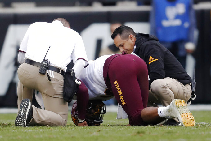Trainers tend to Arizona State quarterback Manny Wilkins, center, after he was hit while throwing a pass late in the second half of an NCAA college football game against Colorado Saturday, Oct. 6, 2018, in Boulder, Colo. Colorado won 28-21. (AP Photo/David Zalubowski)