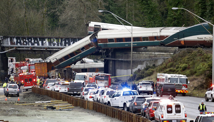 FILE - In this Dec. 18, 2017, file photo, cars from an Amtrak train lay spilled onto Interstate 5 below as some remain on the tracks above in DuPont, Wash. The National Transportation Safety Board has published its final report Monday, June 24, 2019, on a deadly Amtrak derailment in Washington state in 2017, with the agency's vice chairman blasting what he described as a