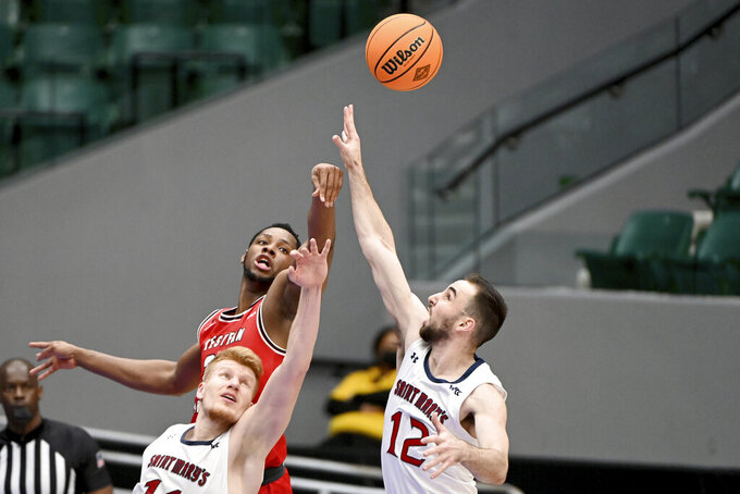 Western Kentucky center Charles Bassey (23) goes after a rebound with St. Mary's forward Matthias Tass (11) and guard Tommy Kuhse (12) in the first half of an NCAA college basketball game in the first round of the NIT, Wednesday, March 17, 2021, in Frisco, Texas. (AP Photo/Matt Strasen)