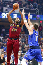 Cleveland Cavaliers' Tristan Thompson (13) shoots over Dallas Mavericks' Luka Doncic (77) in the first half of an NBA basketball game, Sunday, Nov. 3, 2019, in Cleveland. (AP Photo/Ron Schwane)