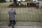 Rev. Robert Turner, with Vernon A.M.E Church, prays as crews work on a second test excavation and core sampling, Tuesday, Oct. 20, 2020, in the search for remains at Oaklawn Cemetery in Tulsa, Okla., from the 1921 Tulsa Race Massacre. (Mike Simons/Tulsa World via AP)