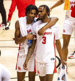 Houston guard Tramon Mark (12), left, and guard DeJon Jarreau (3) walk off the court after defeating Cleveland State in a first-round game in the NCAA men's college basketball tournament, Friday, March 19, 2021, at Assembly Hall in Bloomington, Ind. (AP Photo/Doug McSchooler)