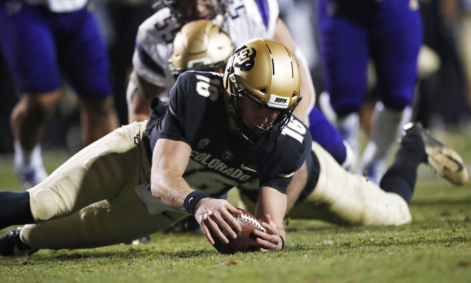 Colorado quarterback Blake Stenstrom, front, recovers a fumble as Washington linebacker Ryan Bowman watches during the second half of an NCAA college football game Saturday, Nov. 23, 2019, in Boulder, Colo. Colorado won 20-14. (AP Photo/David Zalubowski)