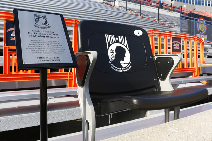 A seat to honor POW * MIA soldiers sits in the end zone before the kickoff of an NCAA football game between Auburn and Alabama State Saturday, Sept. 11, 2021, in Auburn, Ala. (AP Photo/Butch Dill)